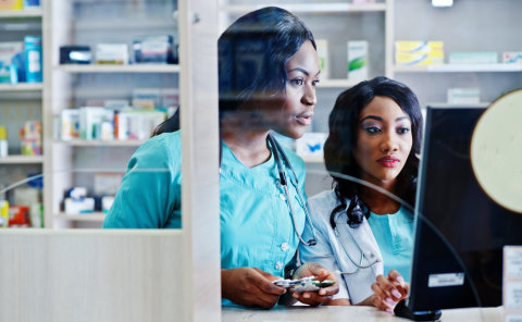 2 pharmacists checking the medicine info on the computer