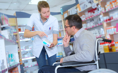 pharmacist explaining the medicine's information to a man in wheelchair inside the pharmacy