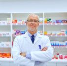 pharmacist in a pharmacy with medicines behind him